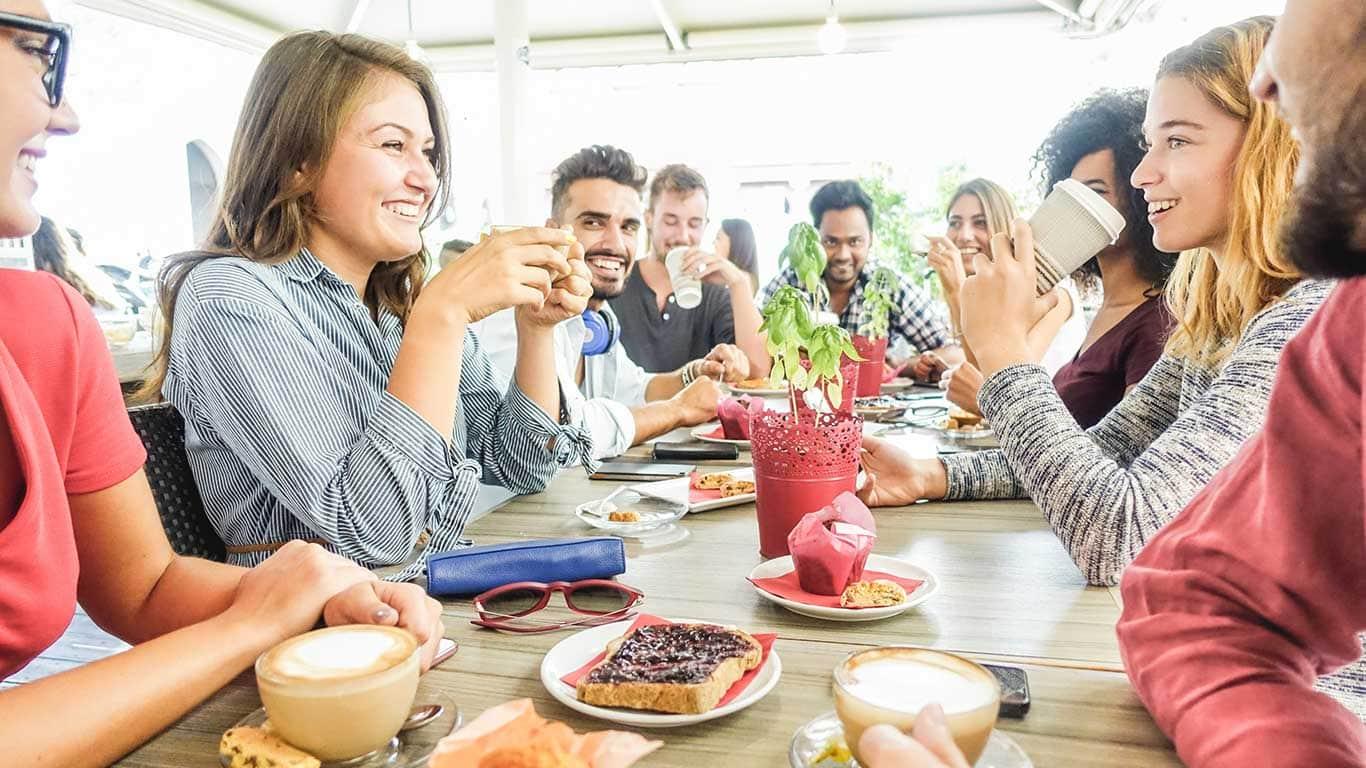 Millennials essen gemeinsam am Tisch.