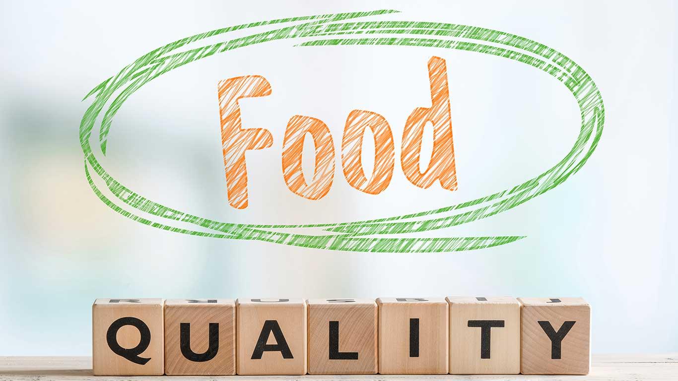 Zeichen für Lebensmittelqualität aus Holzwürfeln auf einem Tisch