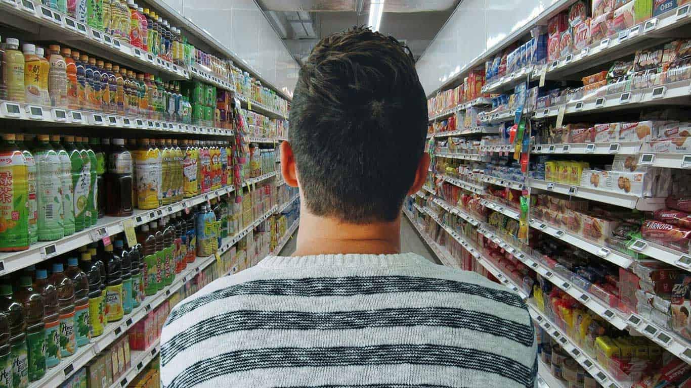 Mann steht im Supermarkt mit Blickrichtung in den Gang.